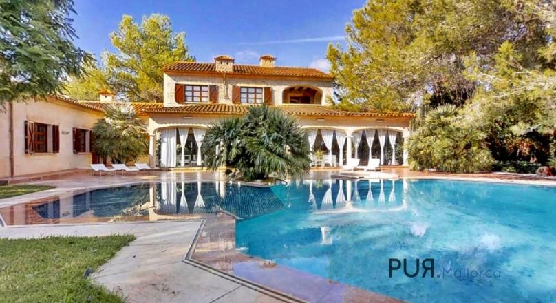 Private villa with stone facade in a lush garden.